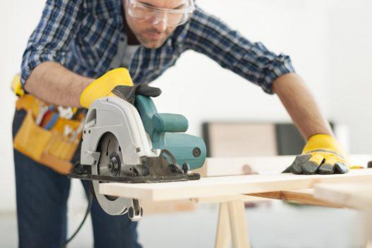Tømrer der saver oven på arbejdsbukke
